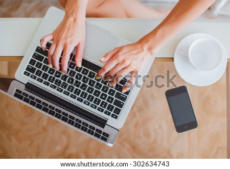 young girl woman working on a laptop sitting at home write messages to drinking coffee smiling typing on a keyboard, macbook serfing, applet style, iphone, - stock photo