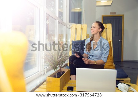 Young girl working with a digital tablet. Woman in a place of rest for office space. Read news or e-book with touch pad. Take a break for rest and relaxation. Favorite work. Freelancer or office staff - stock photo