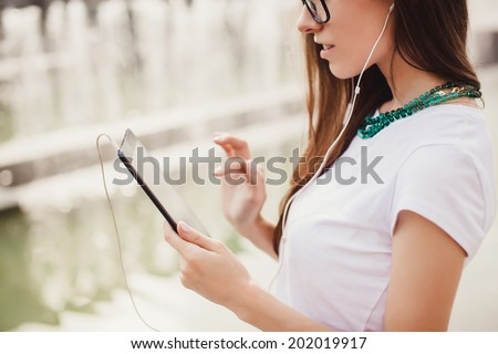 young girl working with tablet in the street - stock photo