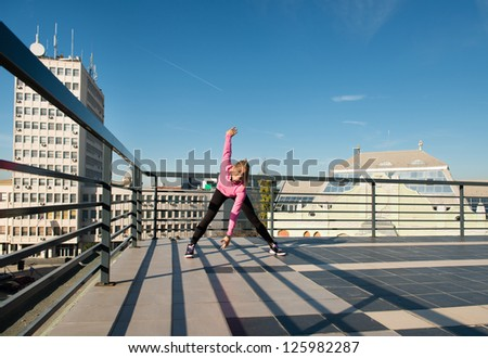 young girl workout on top of the building - stock photo