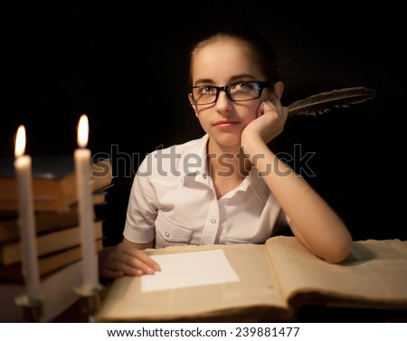 Young girl writing with feather. Candle and book near - stock photo