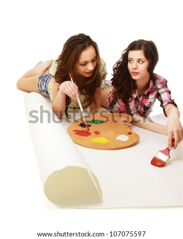 Young girls are painting and lying on the floor - on white background - stock photo