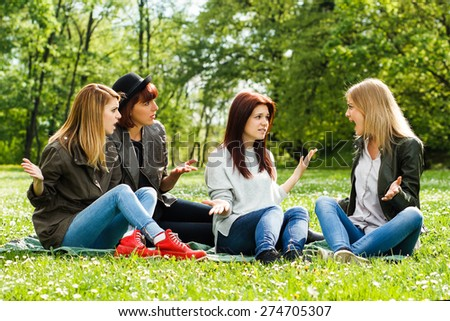 Young girls are sitting in the park and arguing because of something.Conflicts between friends - stock photo