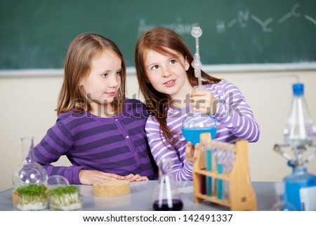Young girls doing a chemistry experiment standing examining a blue mixture in a glass flask at a counter in the classroom - stock photo