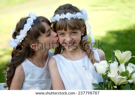 Young girls doing their catholic first holy communion - stock photo