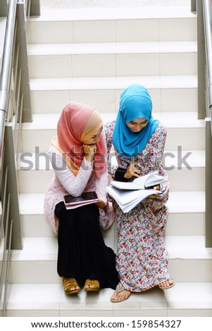 Young Girls in scarf are having some discussions about subject - stock photo