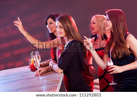 Young girls ordering drinks at the bar in nightclub - stock photo