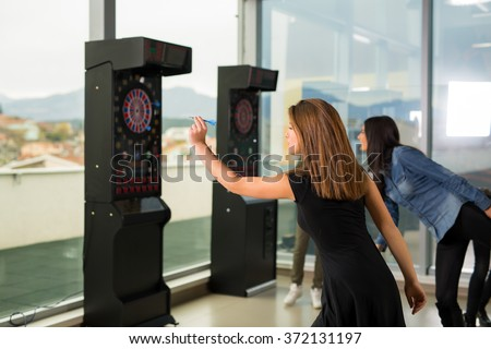 Young girls playing darts in a club  - stock photo