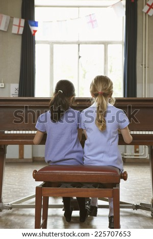 Young Girls Playing Piano - stock photo