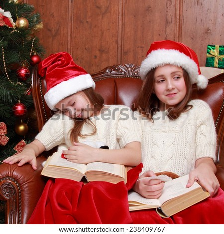young girls sitting in vintage arm chair pretend sleeping and waiting on Santa's presents/Charming caucasian sisters with red and white Santa's hat sleeping snuggled together on Holiday theme - stock photo