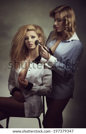 young girls with erotic fashion style, creative hair-style and cute make-up applying blush and wearing open shirt.    - stock photo