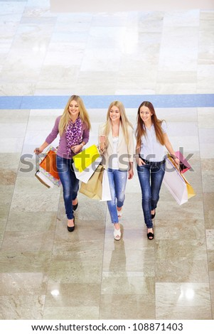 Young girls with shopping bags walking in the store - stock photo
