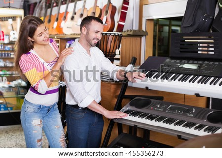 Young  glad happy couple choosing synthesizer in music instruments shop - stock photo