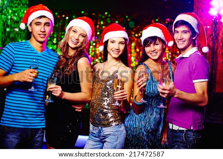 Young glamorous friends in Santa caps looking at camera while toasting with champagne - stock photo