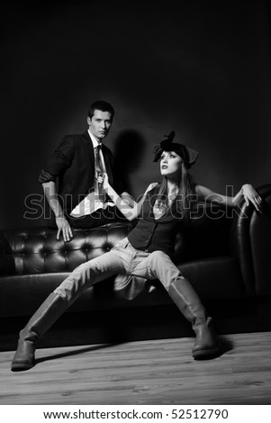 Young glamorous loving couple on a black sofa. Woman pulling man's red tie. Monochrome. - stock photo