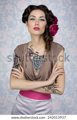 Young glamour attractive sexy european brunette girl with beautiful tattoo paint on her chest and arms posing for fashion photo shoot with red rose in her long hair in front of color floral background - stock photo