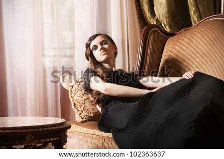 Young glamour woman sitting on armchair - stock photo