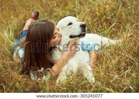 Young golden retriever for a walk with his owner. Dog breed labrador with woman outdoors - stock photo