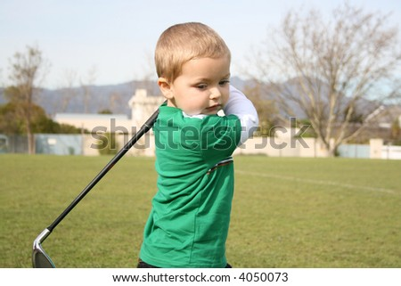 Young golfer concentrating during a practice session on the range - stock photo