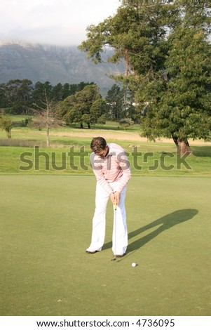 Young golfer during a putt on the golf course - stock photo