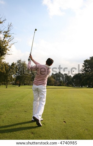 Young golfer during a shot, the grass from the divot still in the air - stock photo