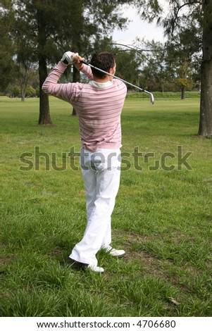 Young golfer following his ball after a shot - stock photo