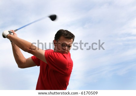 Young golfer hitting a driver against a half cloudy sky - stock photo
