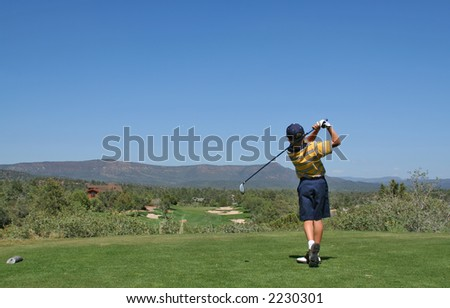 Young golfer hitting a golf ball tee shot in the mountains - stock photo