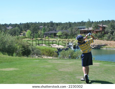 Young golfer hitting a shot over a water hazard - stock photo