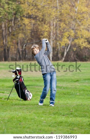 Young golfer playing a shot from the fairway. Blonde caucasian kid. Autumn Season. - stock photo