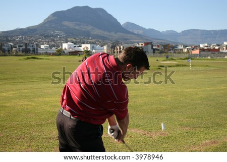 Young golfer practising on the range, the golf ball in flight Follow Through of a young professional golfer whilst practising on the range - stock photo