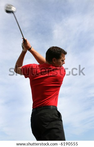 Young golfer with a driver against a blue clouded sky - stock photo