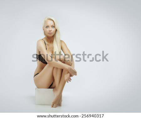 Young gorgeous blond  woman in lingerie sitting - stock photo
