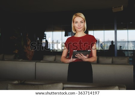 Young gorgeous businesswoman holding in hands digital tablet while standing in modern restaurant interior, successful female CEO dressed in elegant clothes posing while work on portable net-book - stock photo