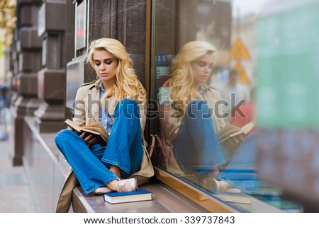 Young gorgeous Caucasian female with perfect look reading book while sitting on a shop sill in warm autumn day, attractive woman dressed with style enjoying calm and rest during her recreation time - stock photo