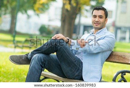 Young gorgeous man sitting on bench in a park, outdoor - outside - stock photo
