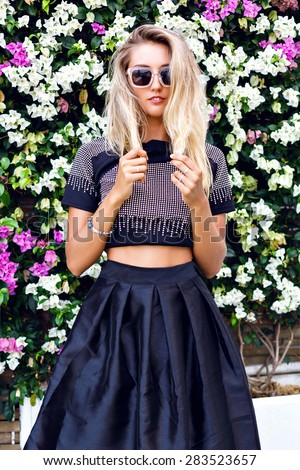 Young gorgeous stunning blonde young woman , wearing stylish outfit, midi skirt, trendy sparkled crop top and sunglasses, posing in floral garden background, beautiful summer day. - stock photo