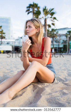 Young gorgeous woman hold cell phone while sitting alone on a beach in a summer day,beautiful blonde hair caucasian female waiting for a call from someone on her smart phone while resting on coastline - stock photo