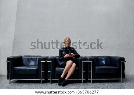 Young gorgeous woman viewing photos on mobile phone while sitting in modern office interior, attractive female designer with cool look reading text message on cell telephone during work break  - stock photo
