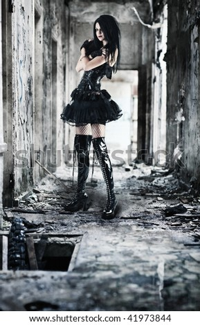 Young goth woman in ruined building. Contrast colors. - stock photo