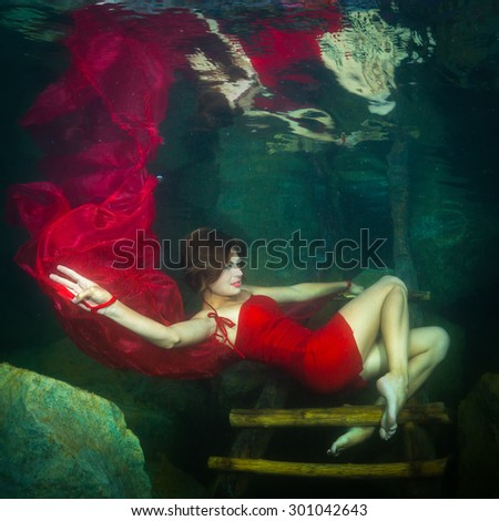 Young graceful woman in a red dress posing near the stairs in the lake - stock photo