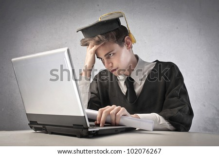 Young graduate student using a laptop - stock photo