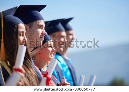 young graduates students group  standing in front of university building on graduation day - stock photo