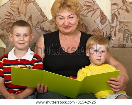 young grandmother with two grandchildren at home on the couch - stock photo