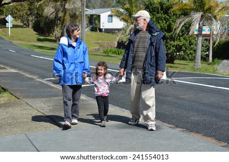 Young grandparents hold hand and walking with their granddaughter outdoor during the autumn. - stock photo