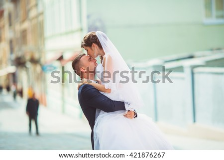 Young groom holding bride on hands  - stock photo