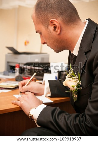 Young groom signing wedding document - stock photo