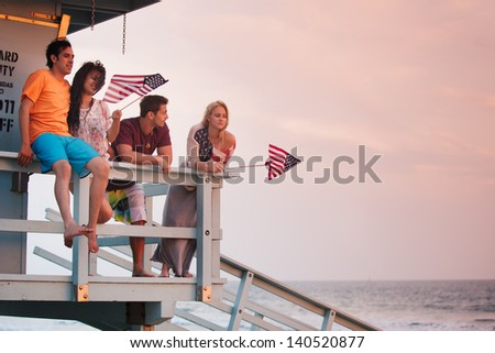 Young Group of Friends at the Beach at Sunset with American Flags - stock photo