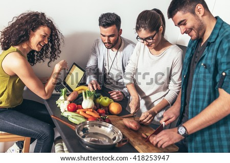 Young group of friends preparing vegetable meal and making fun. - stock photo