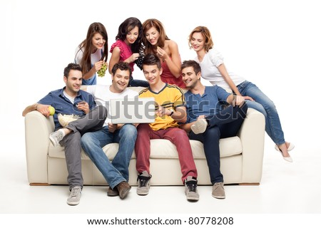 young group of friends sitting on couch smiling at laptop - stock photo